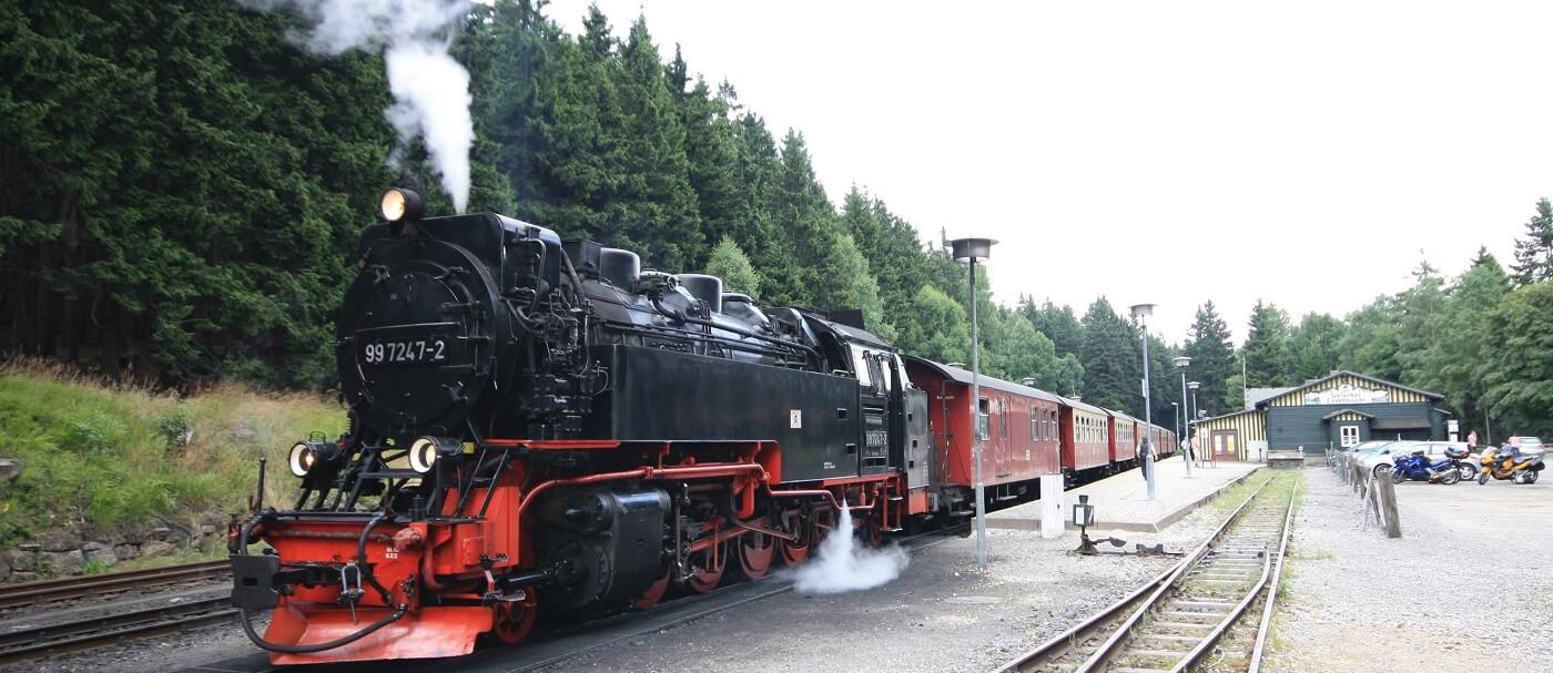 Dampflokomitive der Brockenbahn der Harzer Schmalspurbahn am Bahnhof Schierke mit Dampf und Personenwaggons